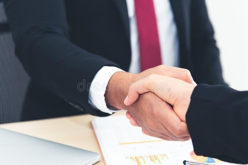 Zakenman en zakenvrouwen schudden na zakelijke overeenkomst, vergadering stock afbeelding