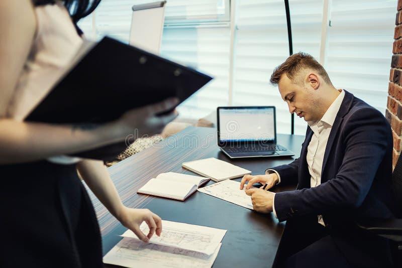 Zakenman en zijn hulpsecretaresse in zijn bureau Secre royalty-vrije stock afbeelding