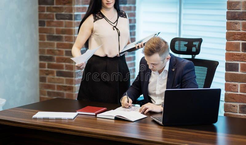 Zakenman en zijn hulpsecretaresse in zijn bureau Secre stock afbeeldingen