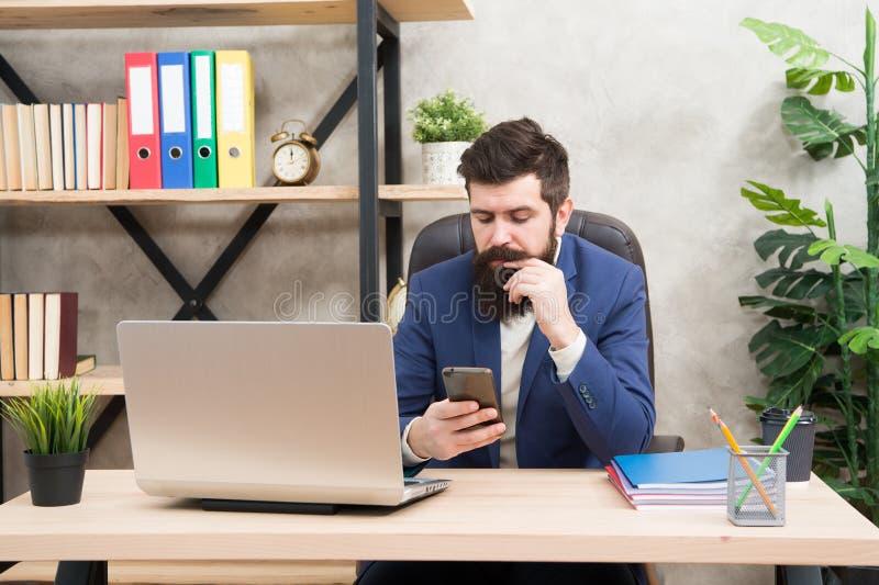 Zakenman in formele uitrusting Zekere laptop van het mensengebruik en mobiele telefoon Het chef- werk met mobiele telefoon Gebaar stock foto's