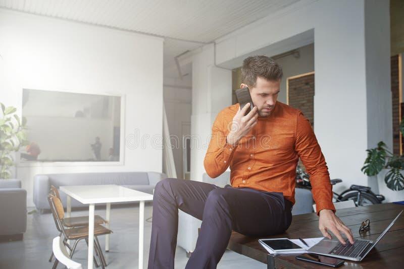 Zakenman gebruikend zijn mobiele telefoon en sprekend met somebody terwijl het zitten bij bureau royalty-vrije stock afbeeldingen