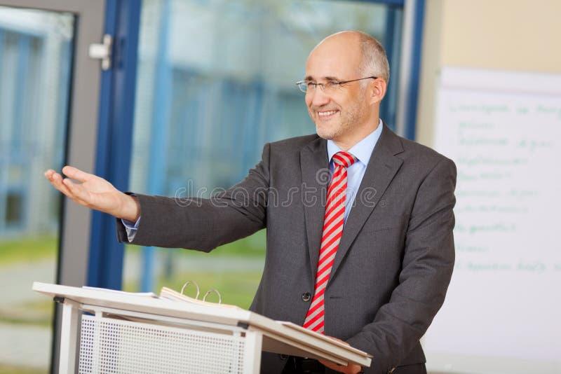 Zakenman Gesturing While Standing bij Podium stock afbeelding