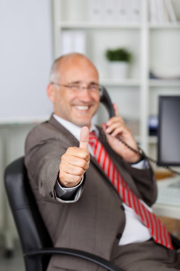 Zakenman Gesturing Thumbs Up terwijl het Gebruiken van Landline Telefoon stock foto
