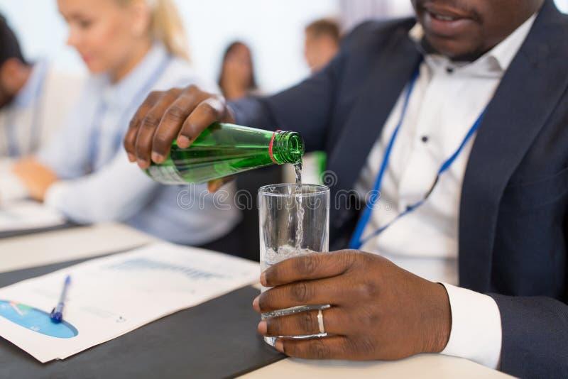 Zakenman gietend water aan glas op conferentie stock afbeelding