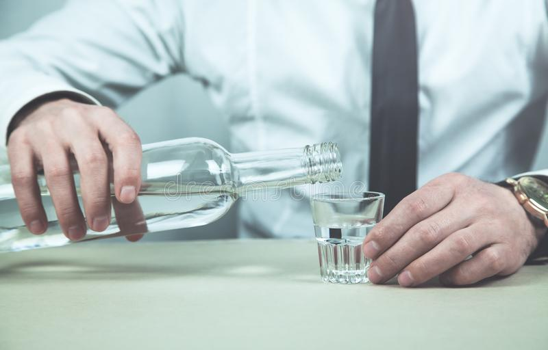 Zakenman gietende wodka in een glas royalty-vrije stock afbeeldingen