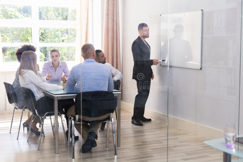 Zakenman Giving Presentation To de Zijn Uitvoerende macht stock afbeelding