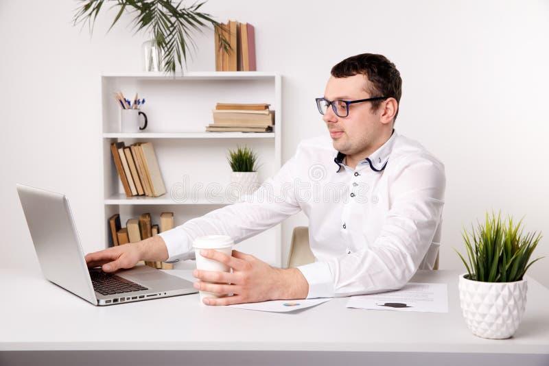 Zakenman in glazen in bureauzitting voor laptop Het drinken van koffie op het werk stock foto