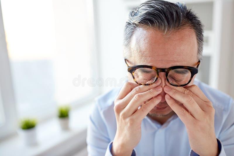 Zakenman in glazen die ogen wrijven op kantoor stock foto's