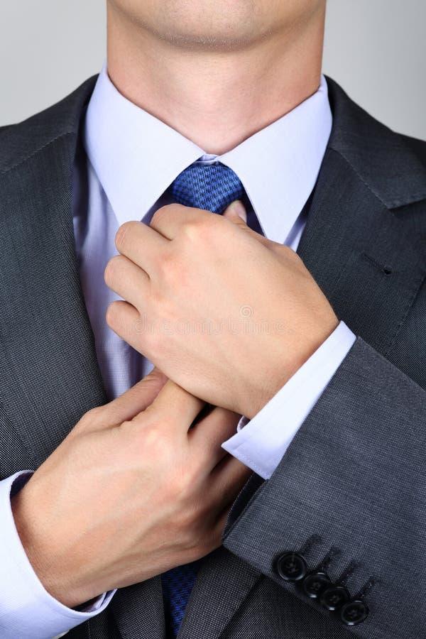 Zakenman in grijs kostuum die de stropdas binden stock afbeeldingen