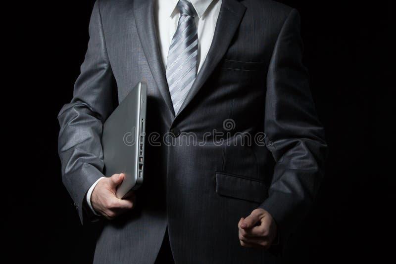 Zakenman in grijze laptop van de kostuumholding in één wapen royalty-vrije stock foto's