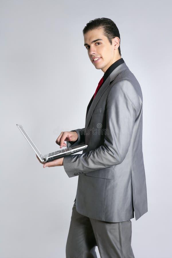 Zakenman in grijze laptop van de kostuumholding stock fotografie