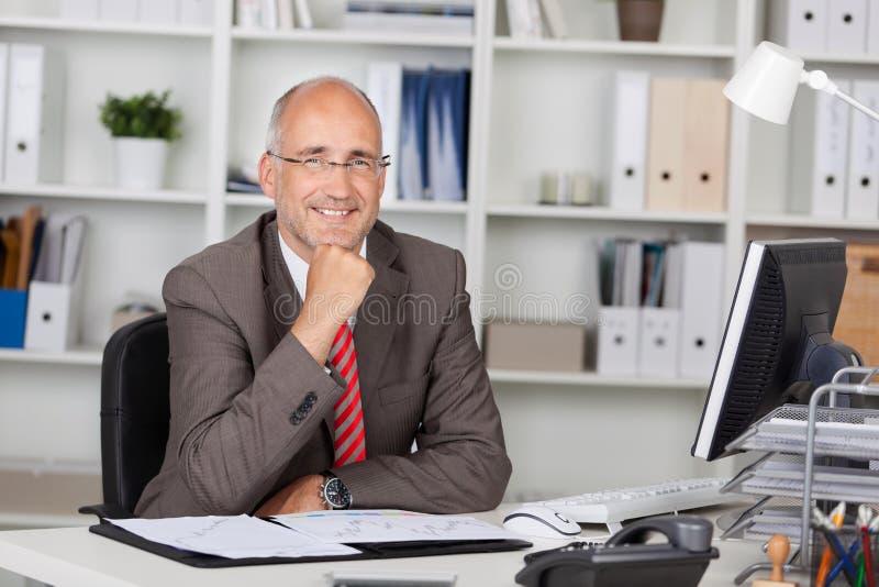 Zakenman With Hand On Chin Sitting At Desk royalty-vrije stock afbeeldingen