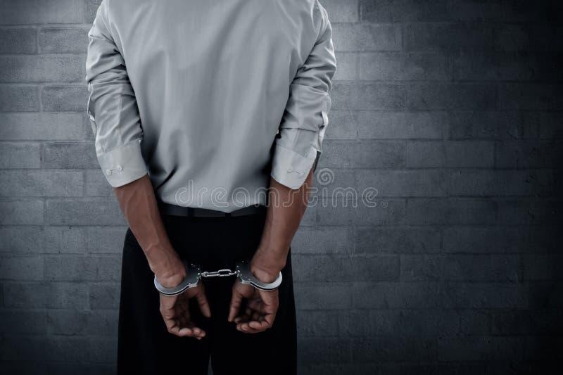 Zakenman in handcuffs op muurachtergrond stock afbeeldingen