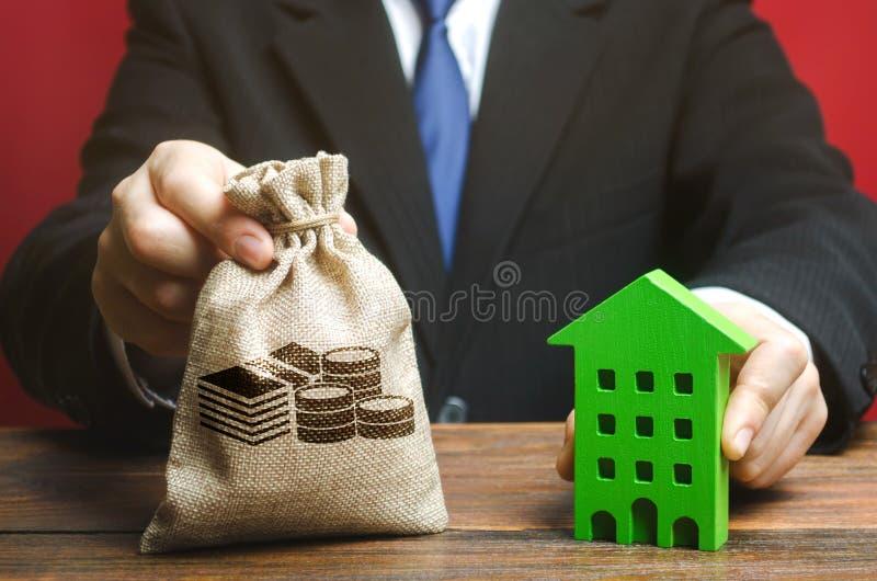 Zakenman heeft een geldzak in de buurt van een houten huis Het begrip 'vastgoedbelegging' Ontwikkelaar Belastingen, hypotheken, l stock foto's