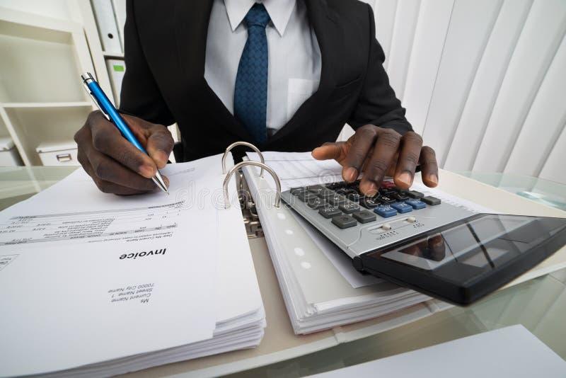 Zakenman het berekenen rekeningen stock afbeelding