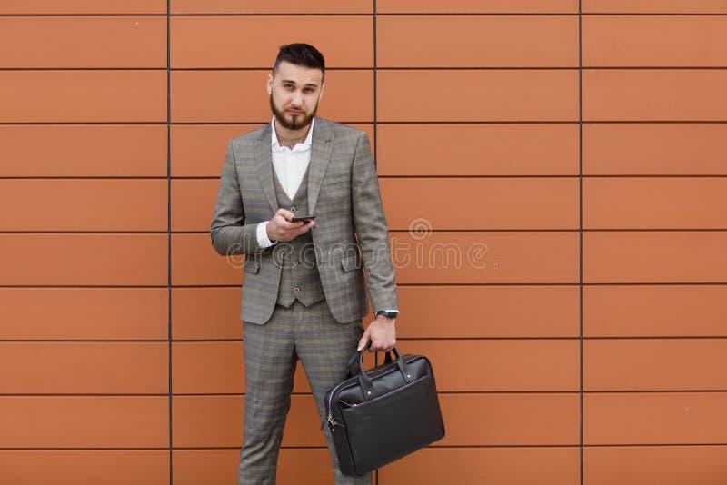 Zakenman het dragen passen en het gebruiken van moderne smartphone dichtbij bureau bij vroege ochtend, succesvolle werkgever om e royalty-vrije stock afbeeldingen