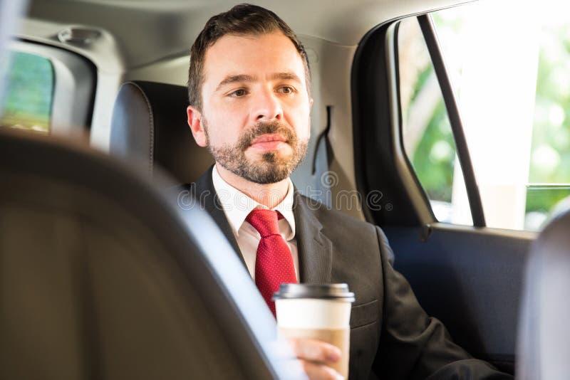 Zakenman het drinken koffie in een auto stock afbeeldingen