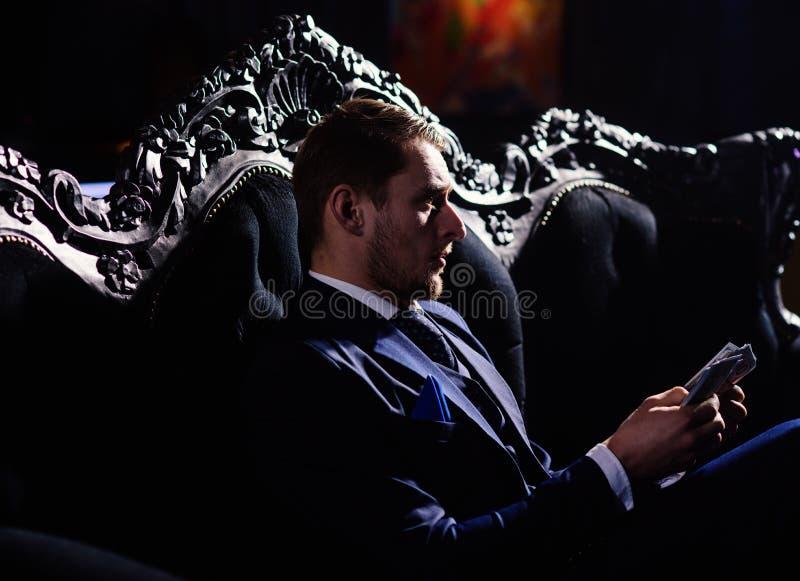 Zakenman in het geld van de kostuumholding in zijn handen Vrijheid, de zitting van de succesmens met geld in sui stock foto's