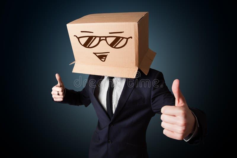 Zakenman het gesturing met een kartondoos op zijn hoofd met smileygezicht stock afbeelding