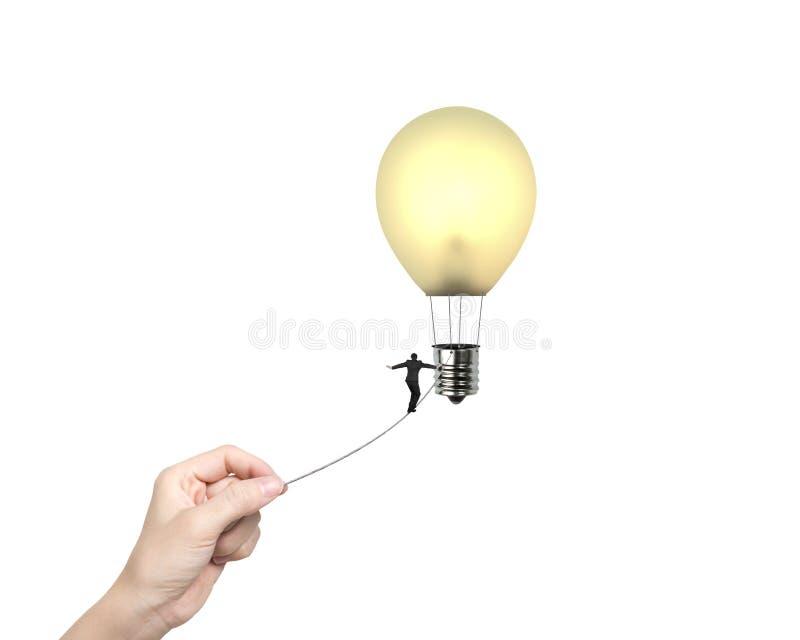 Zakenman het lopen de hand die van de strak koordvrouw lightbulb hete a trekken stock fotografie