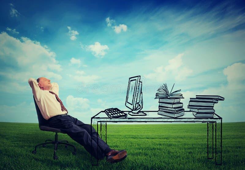 Zakenman het ontspannen bij zijn bureau in het midden van groene weide royalty-vrije stock foto