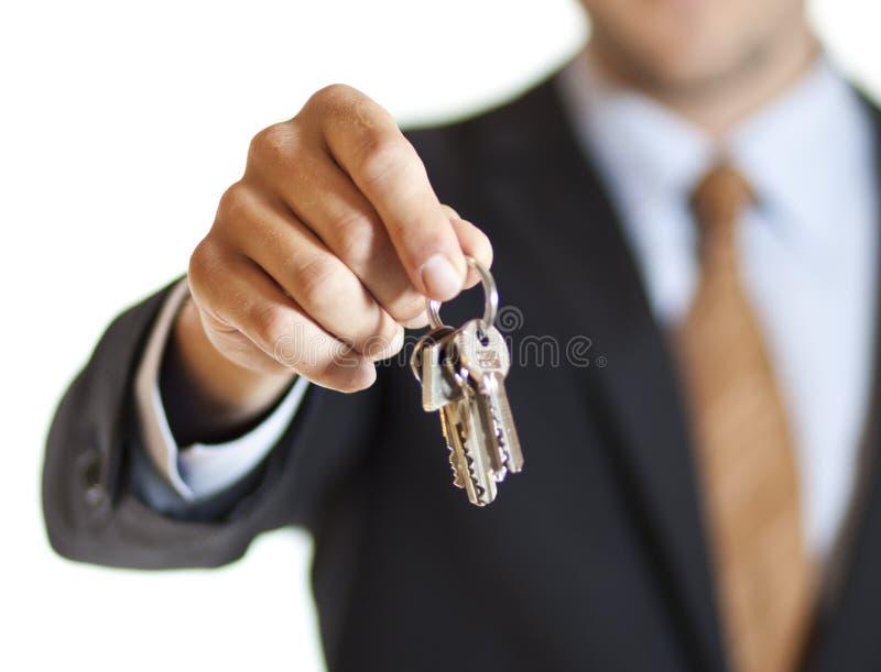 Zakenman het overhandigen sleutels stock afbeelding