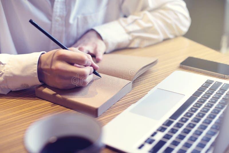 Zakenman het schrijven de tekst in notitieboekje en bekijkt geopende laptop in koffie, openbare mede-werkt ruimte Het hebben van  royalty-vrije stock afbeeldingen
