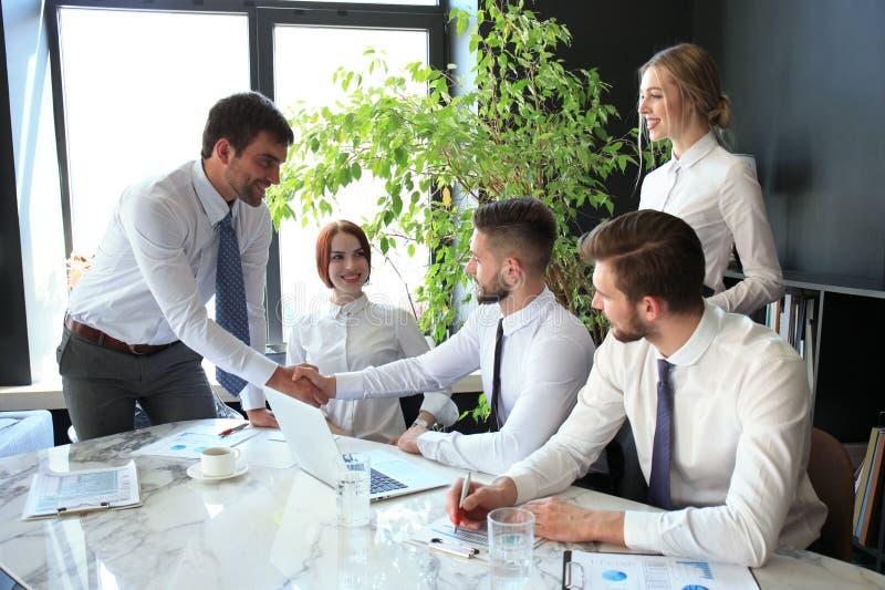 Zakenman het schudden de handen om te verzegelen behandelen zijn partner en collega's in bureau royalty-vrije stock afbeelding