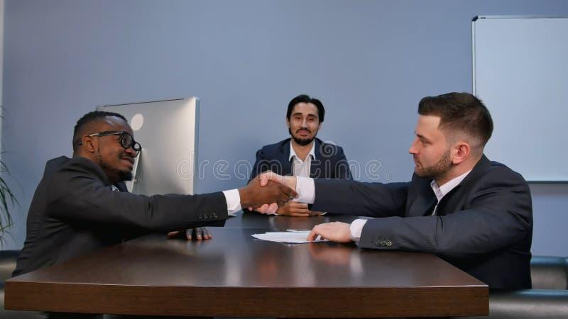 Zakenman het schudden de handen om te verzegelen behandelen zijn partner tijdens vergadering stock afbeelding