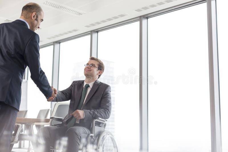 Zakenman het schudden handen met glimlachende gehandicapte collega in bestuurskamer tijdens vergadering op kantoor royalty-vrije stock afbeelding
