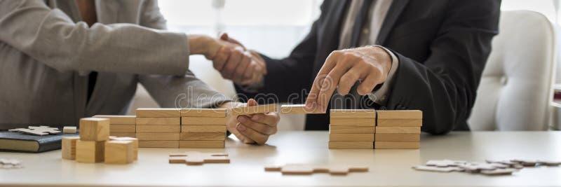 Zakenman het schudden handen met houtsneden op bureau royalty-vrije stock fotografie
