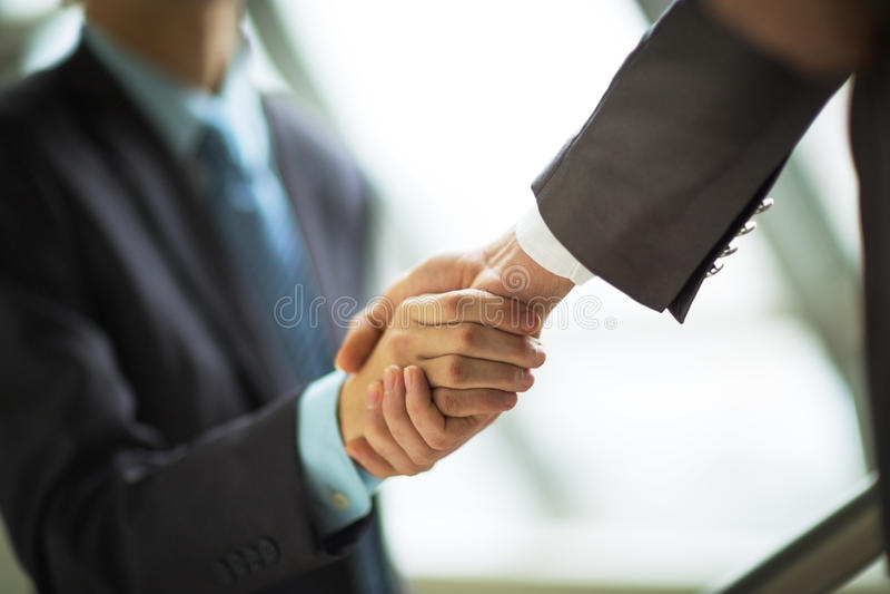 Zakenman het schudden handen om een overeenkomst te verzegelen stock afbeeldingen