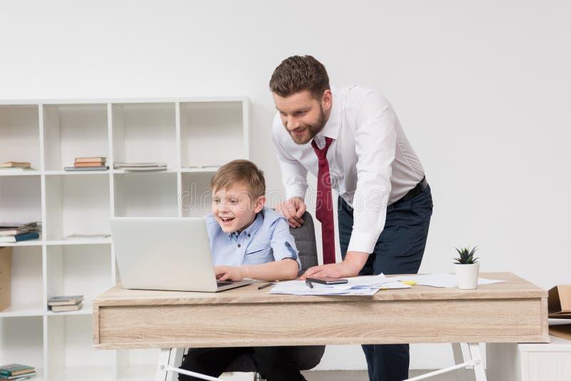 Zakenman het spelen op laptop met zijn zoon stock foto