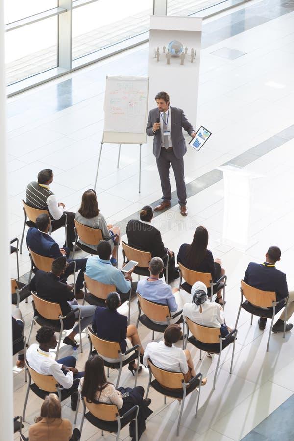Zakenman het spreken met digitale tablet spreekt in een bedrijfsseminarie royalty-vrije stock afbeelding