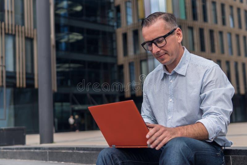 Zakenman in het toevallige werken aan laptop stock fotografie