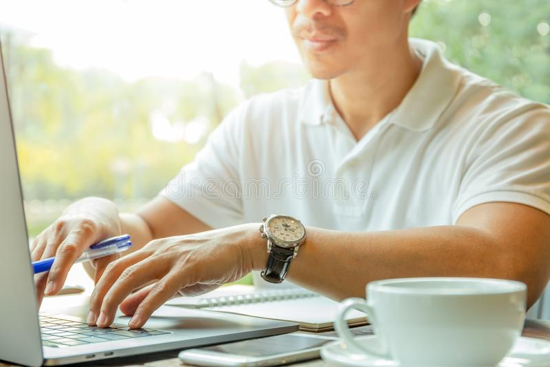 Zakenman het typen op laptop computer terwijl het zitten in koffie met kop van koffie stock afbeelding