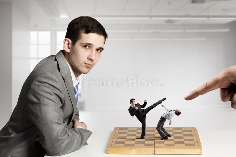 Zakenman het vechten op het schaakbord royalty-vrije stock afbeeldingen