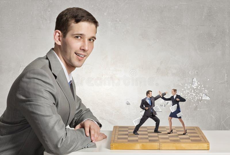 Zakenman het vechten op het schaakbord stock foto's