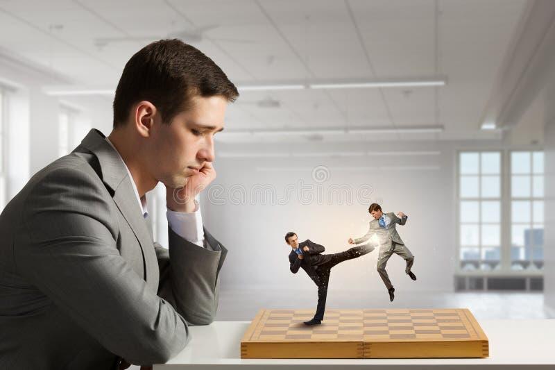 Zakenman het vechten op het schaakbord stock afbeeldingen