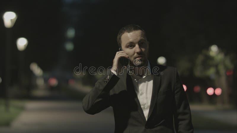 Zakenman het vriendschappelijke spreken telefonisch in stadspark in goede stemming stock fotografie