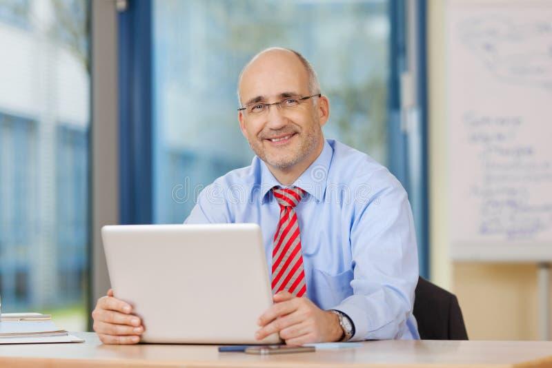 Zakenman Holding Digital Tablet bij Bureau royalty-vrije stock foto