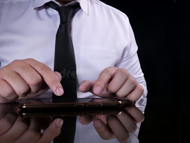 Zakenman Holding en het Gebruiken van Smartphone stock afbeeldingen
