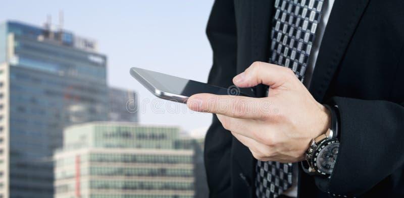 Zakenman Holding Smartphone die in Hand en een Bericht met Commerciële Stad en Collectieve Gebouwen op Achtergrond typen stock fotografie