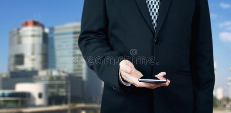 Zakenman Holding Smartphone ter beschikking met Commerciële Stad en Collectieve Gebouwen op Achtergrond royalty-vrije stock afbeeldingen