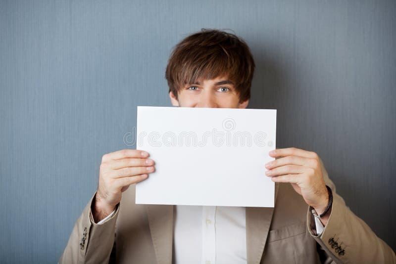 Zakenman Holding White Paper tegen Blauwe Muur royalty-vrije stock fotografie