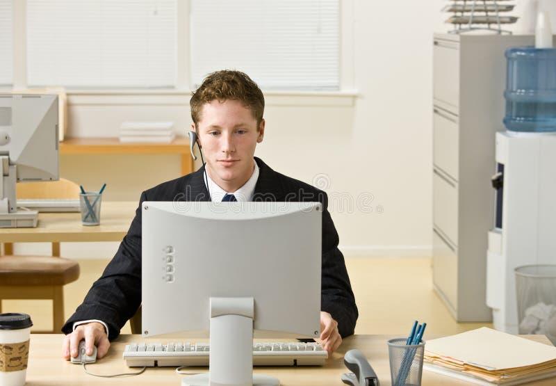 Zakenman in hoofdtelefoon die bij computer werkt royalty-vrije stock fotografie