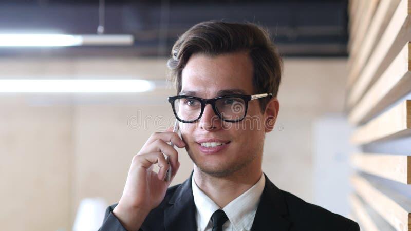 Zakenman in Kostuum die bij Smartphone, het Glimlachen en het ontspannen spreken stock foto