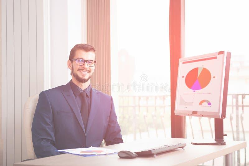 Zakenman in kostuum die bij zijn computer naast een glaswind werken royalty-vrije stock foto