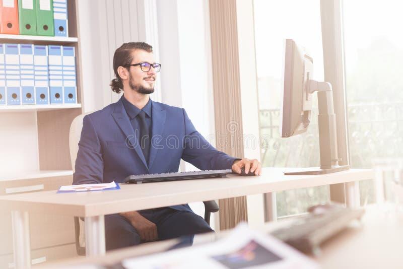 Zakenman in kostuum die bij zijn computer naast een glaswind werken stock fotografie