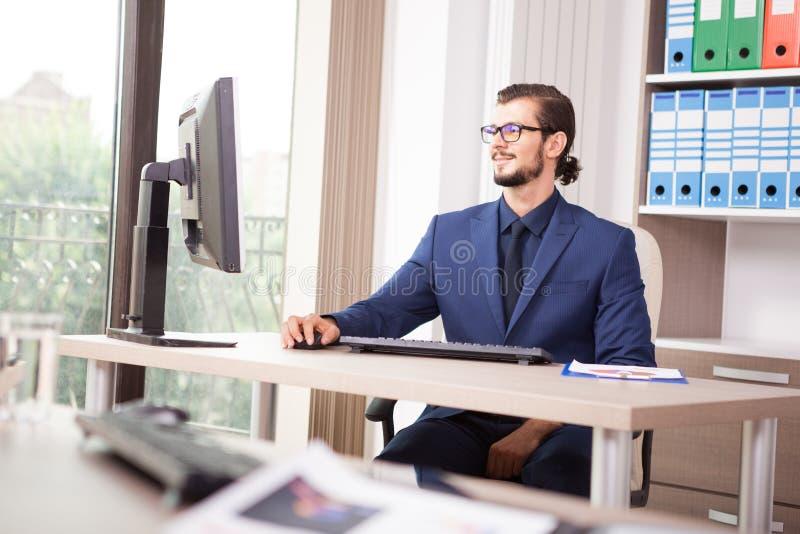 Zakenman in kostuum die bij zijn computer naast een glaswind werken royalty-vrije stock foto's